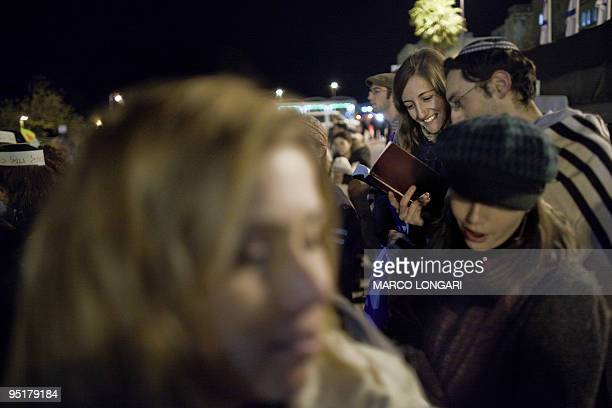 Jewish couple covered with a prayer shawl worn customarily by men only attend a prayer service at the Western Wall Plaza held by the Women at the...