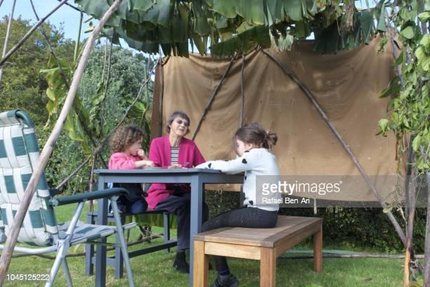 jewish family sitting in a sukkah on sukkoth feast of tabernacles jewish holiday - rafael ben ari - fotografias e filmes do acervo