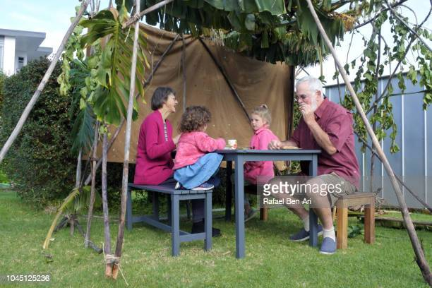 jewish family sitting in a sukkah on sukkoth feast of tabernacles jewish holiday - rafael ben ari stock pictures, royalty-free photos & images