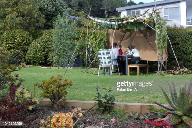 jewish family sitting in a sukkah on sukkoth feast of tabernacles jewish holiday - 仮庵の祭り ストックフォトと画像