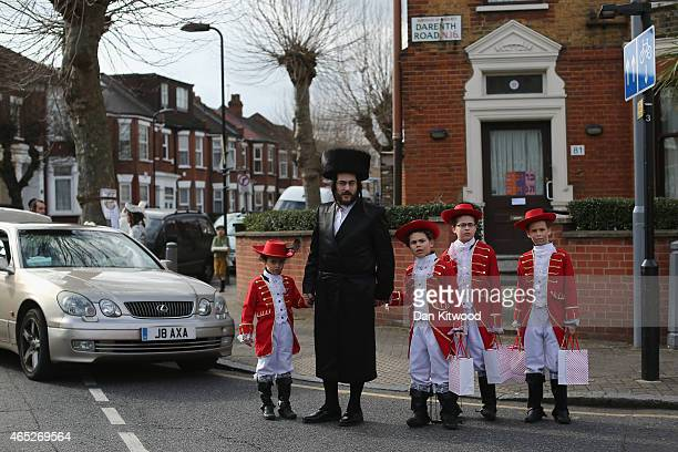 Jewish family with children in fancy dress walk through the streets collecting money for their school during the Jewish holiday of Purim on March 5...