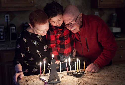 Jewish Family with granparents and grandson lighting Hanukkah Candles in a menorah for the holidays 674407486