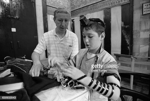 A Jewish father teaches his son to lay Tefillin for prayers in Hebron