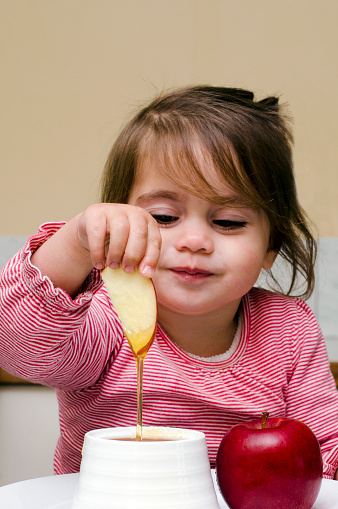 Jewish girl dipping apple slices into honey 688292078
