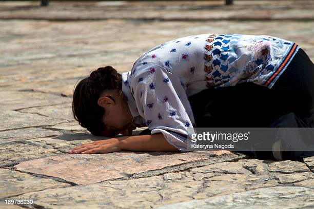 CONTENT] Jewish girl is praying on her knees by the Wailing wall in Jerusalem Israel