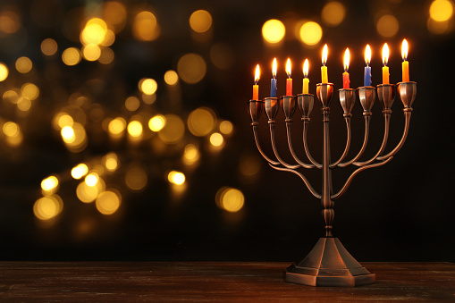 jewish holiday Hanukkah background with menorah (traditional candelabra) and burning candles 869797744