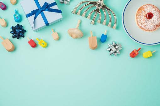 Jewish holiday Hanukkah background with menorah, sufganiyot, gift box and spinning top 1063306860