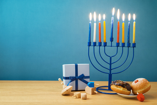 Jewish holiday Hanukkah background with menorah, sufganiyot, gift box and spinning top on wooden table 1068881748