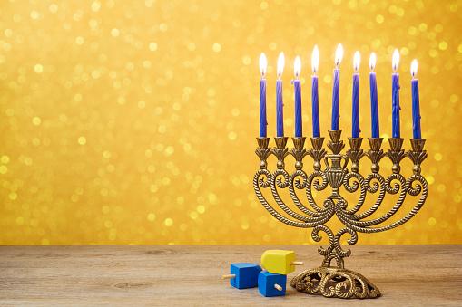 Jewish holiday Hanukkah background with vintage menorah and spinning top dreidel over lights bokeh. 868015174