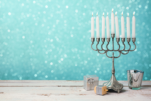 Jewish holiday Hanukkah celebration with menorah, dreidel and gifts on wooden table 868015234