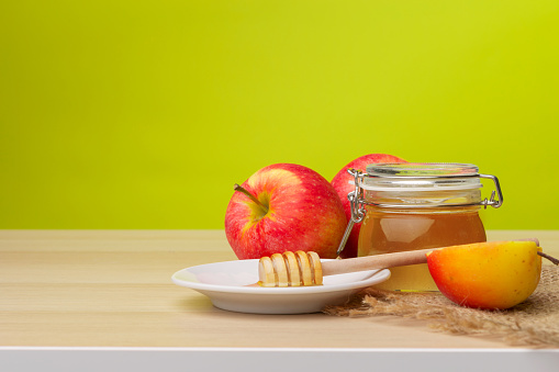 Jewish holiday Rosh Hashanah background with honey and apples on wooden table. 1144373561