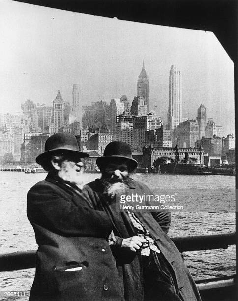 Jewish immigrants at Ellis Island, with the skyscrapers of New York in the background.