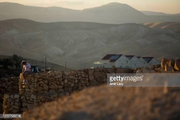 Jewish Israeli boy sits on a fence in the Jewish settlement of Mizpe Yericho in the Jordan Valley West Bank on June 24, 2020 in Mizpe Yericho, West...