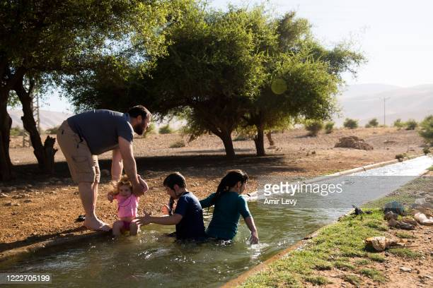 Jewish Israeli family hang out in the water of the natural spring of Ein Al-AUJA in the Jordan Valley West Bank on June 24, 2020 in Ein Al -Auja,...