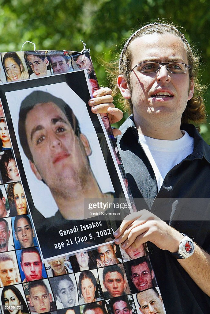 Jewish Israeli students hold photos of victims of Palestinian terror during their demonstration outside the Tel Aviv District Court during the judgement hearing of Marwan Barghouti, on May 20, 2004, in Tel Aviv, Israel. Barghouti, the head of the Palestinian Fatah Tanzim and al-Aksa Martyrs Brigades, was convicted of five counts of murder.