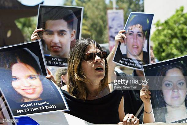 Jewish Israeli students hold photos of victims of Palestinian terror during their demonstration outside the Tel Aviv District Court during the...