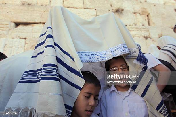 A Jewish man and his children covered with the Talit attend the Cohanim prayer at the annual blessing celebration of Sukkot or the feast of the...