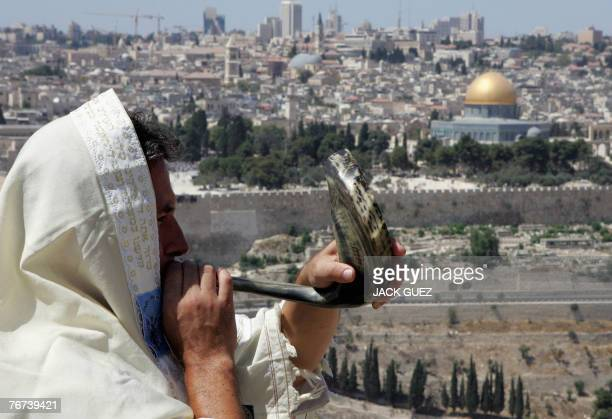 A Jewish man blows a Shofar or Ram's horn as he stands at a viewing point on the Mount of Olives overlooking annexed east Jerusalem home to the...