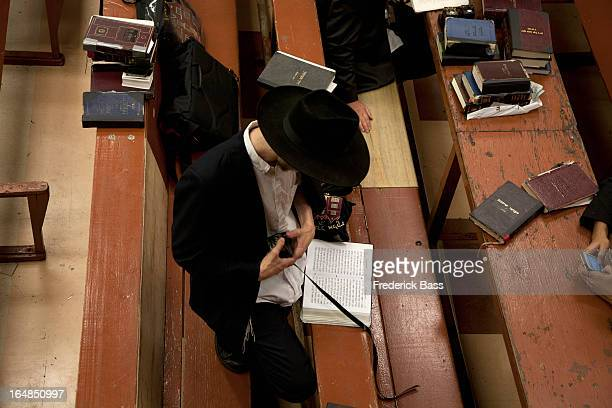 jewish man holding tefillin  in synagogue - strap stock photos and pictures