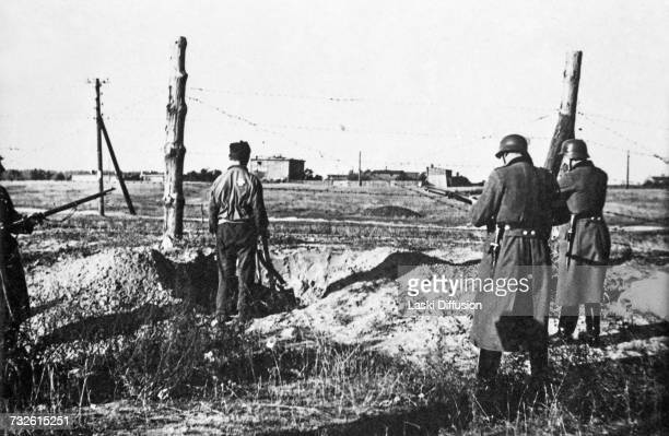 Jewish man is forced to dig his own grave before his execution Lodz 1941 He is wearing a Star of David badge on his back A photo from an album...