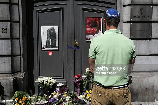 Jewish man pays his respects in front of flowers and a makeshift memorial at the entrance to a Jewish Museum in Brussels where a deadly shooting took...
