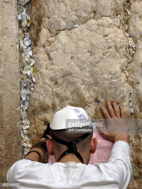 A Jewish man prays at the Western Wall Judaism's most holy site in the Old City of Jerusalem 26 March 2006 Israelis go to the polls in the Jewish...