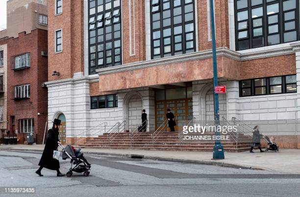 A Jewish man pushes a stroller across a street in a Jewish quarter in Williamsburg Brooklyn on April 9 2019 in New York City New York Mayor Bill de...