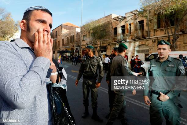 A Jewish man reacts as Israeli police secure the entrance of the central bus station in Jerusalem after a Palestinian stabbed and seriously wounded...