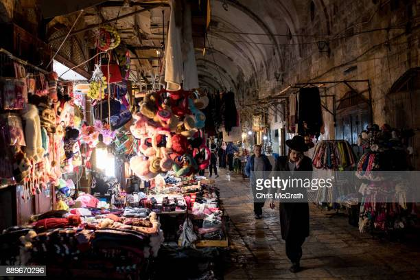 Jewish man speaks on the phone as he passes stores at an entrance to the AlAqsa Mosque in the Old City on December 10 2017 in Jerusalem Israel In an...