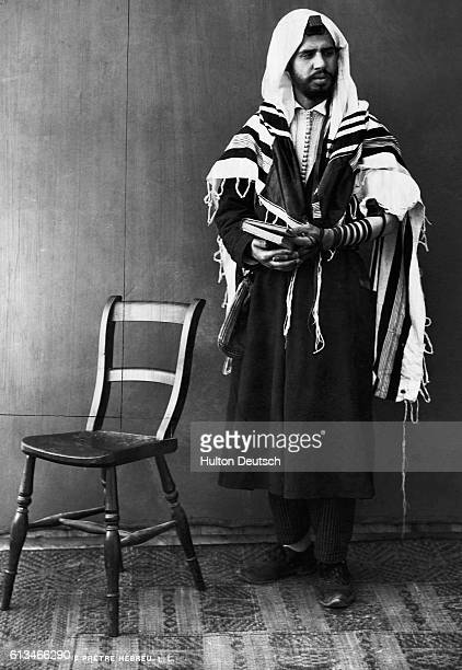 A Jewish man stands next to a chair and prays in a tephilliu and Tallitim or prayer shawl