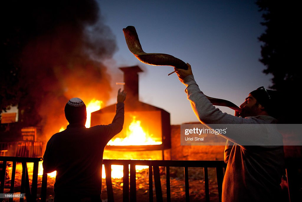 A Jewish man throws votive candles into a burning pyre as another blows a shofar at the grave of Rabbi Yisrael Abuhatzera, known as the sage Baba Sali, on January 15, 2013 in the southern Israeli town of Netivot, Israel. Thousands of Jews, mainly of Moroccan origin, gathered to pray and hold festivities at the tomb of the respected rabbi who was known as a miracle maker by religious Jews.