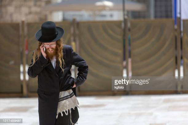 jüdischer mann mit telefon in jüdischen gebetschal und hut an der klagemauer, klagemauer, kotel in jerusalem altstadt, israel - jewish prayer shawl stock-fotos und bilder
