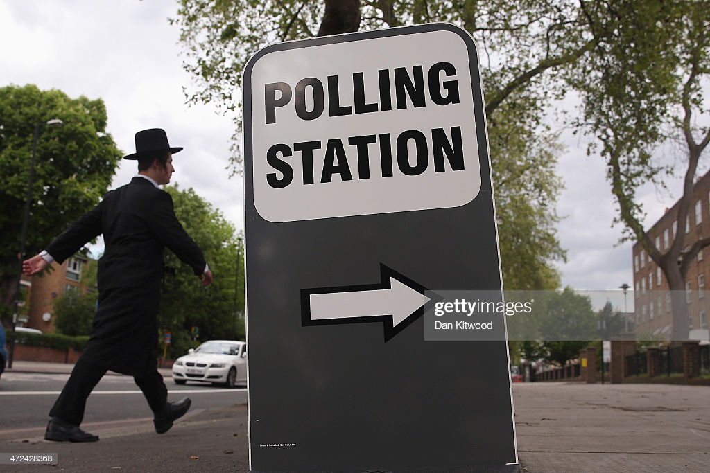A Jewish man walks past a polling station set up inside a residents association office on May 7, 2015 in London, England. The United Kingdom has gone to the polls to vote for a new government in one of the most closely fought General Elections in recent history. With the result too close to call it is anticipated that there will be no overall clear majority winner and a coalition government will have to be formed once again.