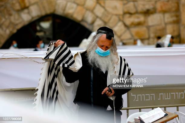 A Jewish man wearing a traditional Tallit prayer shawl and a face mask following tightened restriction aimed at fighting the spread of the novel...