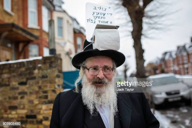 Jewish man with a toilet roll attached to hat to offer out to people in the cold weather is pictured in Stamford Hill during the annual Jewish...