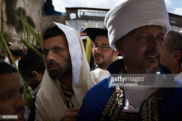 A Jewish man with a white prayer shawl covering his head walks past a Kes as they take part in the Blessing of the Priests ceremony or 'Birkat...