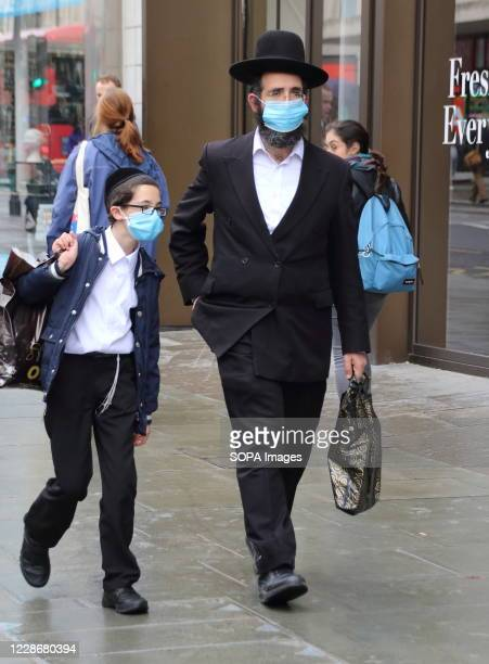 Jewish man with his son walk along Oxford Street while while wearing face masks as a preventive measure against the spread of Coronavirus . Members...