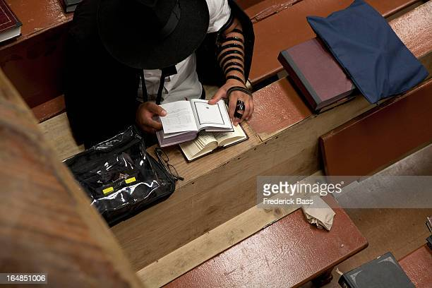 Jewish man with tefillin reading religious prayer book