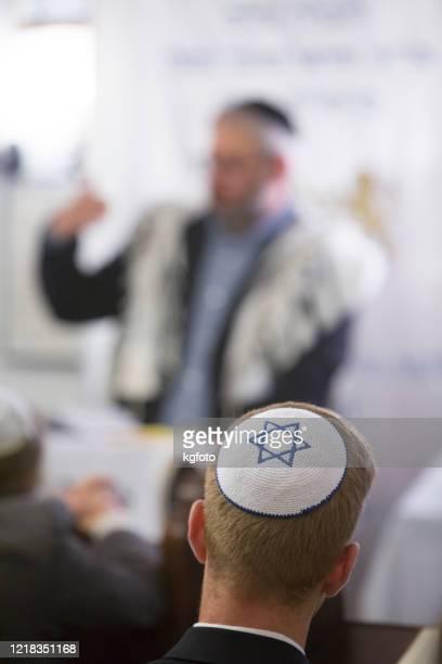 homme juif avec le yarmulke écoutant le rabbin parlant de la torah, bible dans une synagouge juive sur l'événement religieux - celebratory event photos et images de collection