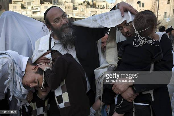 A Jewish man wrapped with a prayer shawl blesses his family during the Annual Cohanim prayer or Priest's blessing for the Pesach holiday at the...