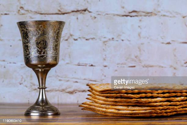 a jewish matzah bread with wine in kiddush cup. passover holiday concept - passover symbols stock pictures, royalty-free photos & images