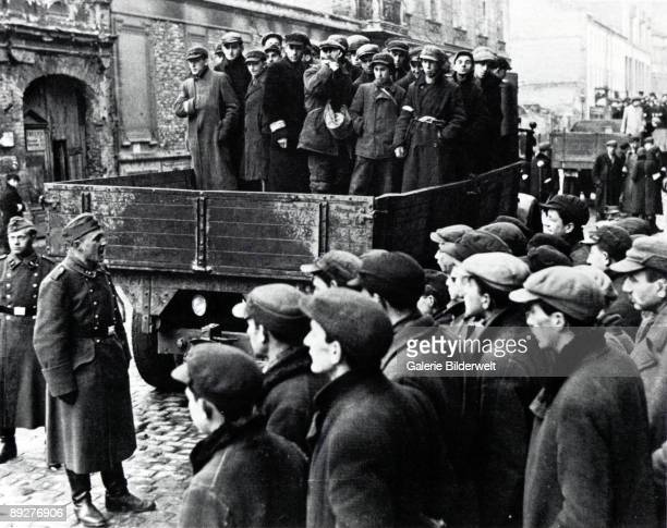 Jewish men are transported from the Warsaw Ghetto by Wehrmacht soldiers, to work on sites elsewhere, Poland, 1941.