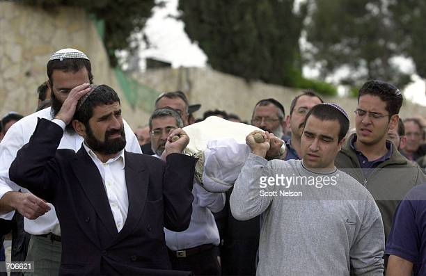 Jewish men carry the prayer shawlcovered body of slain 42yearold Israeli Yitzhak Cohen March 22 2002 in Jerusalems Givat Shaul cemetery Cohen was...