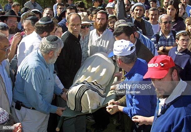 Jewish men carry the shroudcovered body of Dr Shmuel Gillis during his funeral February 2 2001 at the Kfar Etzion regional cemetery in the West Bank...