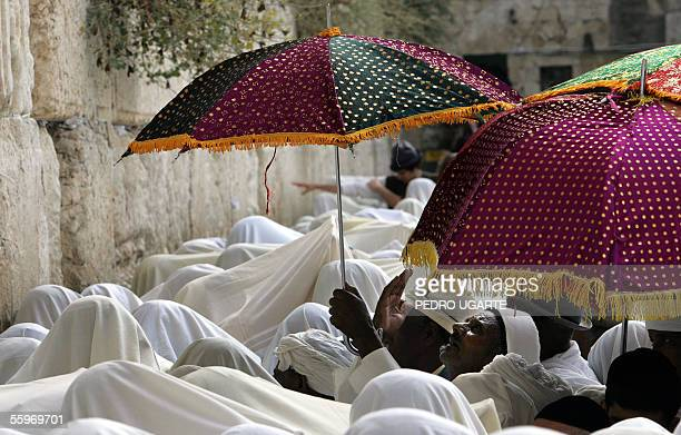 Jewish men cover their heads with Talit prayer shawls as an Ethiopian Jew also know as Falashmora prays under an umbrella during the traditional...