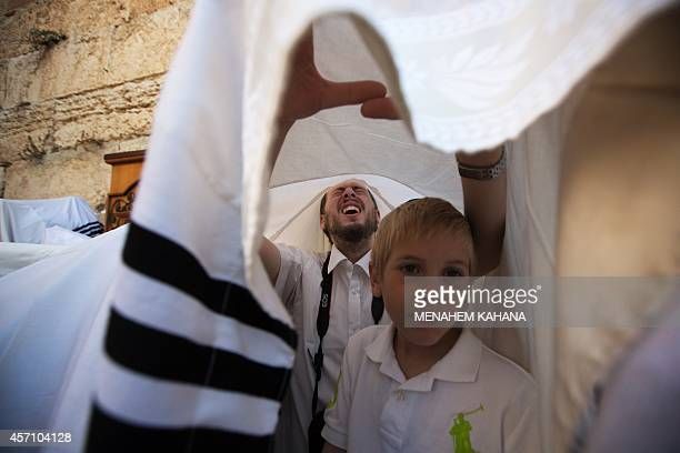 Jewish men draped in prayer shawls perform the annual Cohanim prayer during the Sukkot or the feast of the Tabernacles holiday at the Western Wall in...