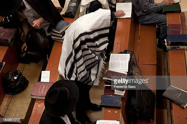 Jewish men in traditional clothing reading religious text