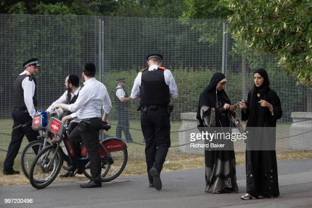 Jewish men Muslim ladies with UK Met police officers who guard a temporary perimeter fence encircling Winfield House the official residence of the US...
