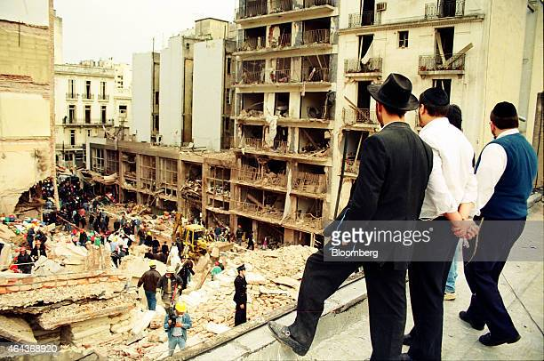 Jewish men right look on as rescuers sift through the rubble at the site of a carbombing at the Asociacion Mutual Israelita Argentina Jewish...