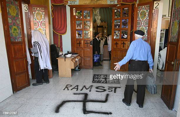 Jewish men stand at the swastikas painted entrance of the grand synagogue in Petach Tikva, near Tel Aviv 04 May 2006. Rabbi Avraham Levine immigrated...